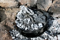 Dutch oven covered by coals