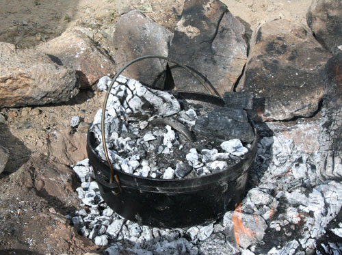 bury a dutch oven in coals for even campfire cooking