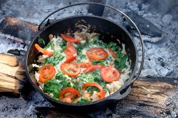 Dutch Oven Hash Browns topped with cheese, spinach and tomatoes