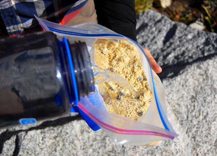 Adding water to Blueberry Cornmeal Pancake batter